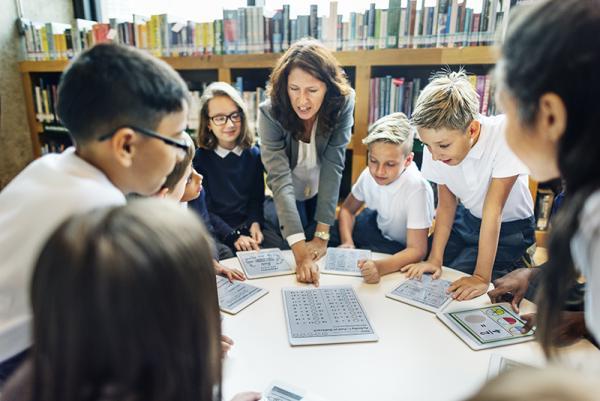 Leerkracht met tablet voor de klas