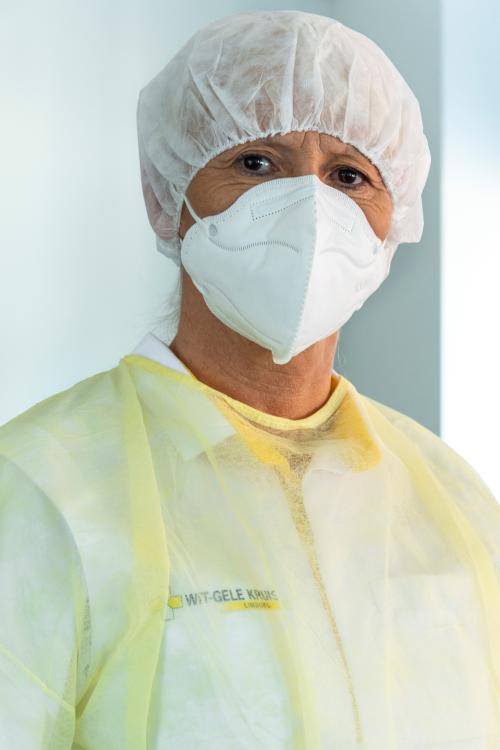 Een medewerker van het Wit-Gele Kruis met een mondmasker