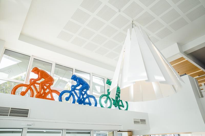Drie 'coureurs' aan de inkom van het gebouw. De oranje fietser (Voka) zet het peloton (de ondernemingen) uit de wind.